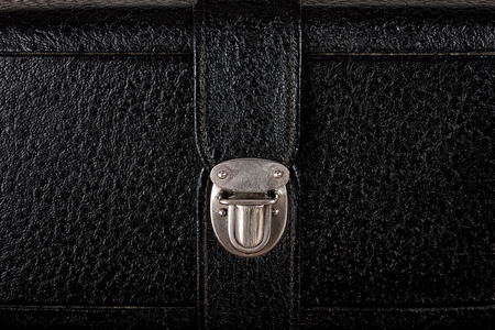 buckle: Metal buckle on vintage case of textured black leather closeup.