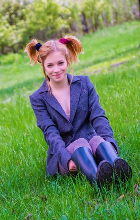 Cheerful young girl with two hair tails in rubber boots sitting on the green grass in a sunny spring day. Stock Photo
