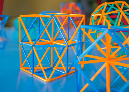 solids: Coloured three-dimensional model of geometric  solids on the blue table defocused.