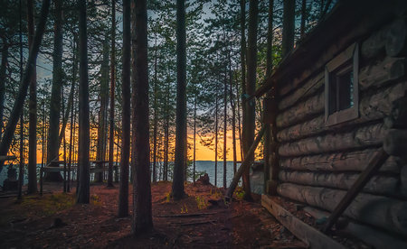 fishing cabin: Old fishing hut in the woods on the shore of Lake Onega at sunset.