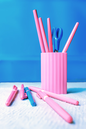 Pink pencil-box with pencils, pens and scissors on a blue background.