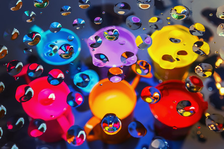 Bright abstract background - view through glass with drops of liquid on a blurry colorful watering cans and buckets. Selective focus on foreground.