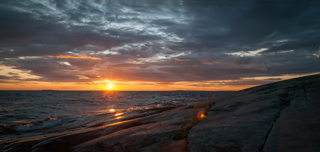 onega: Orange and gray evening seascape. Lake Onega Waves beat against the stone shore which reflects the rays of the setting sun on the background of a dramatic stormy sky.