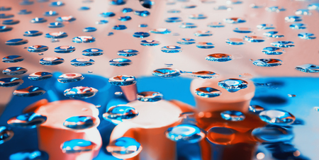 Blurred abstract blue and pink background - view through glass with drops of water on bailers and buckets out of focus.