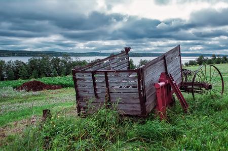 carreta madera: heno metal de la vendimia rastrillos con un viejo vag�n de madera en el fondo del r�o y el cielo nublado dram�tico.