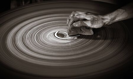 finesse: The hand of unrecognizable person draws by sponge and clay on the potters wheel. Filter sepia, selective focus.