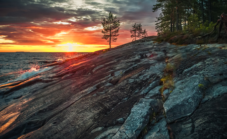 Orange and gray evening  landscape. Dramatic sunset on the territory of Onego petroglyphs in Karelia, Russia.