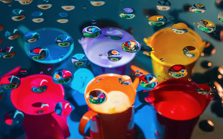 Multicolored abstract background - view through glass with drops of liquid on a blurry colorful watering cans and buckets. Selective focus on foreground. Stock Photo