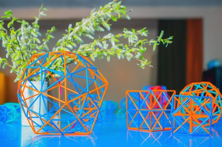 Coloured three-dimensional model of geometric solids de-focused on the blue table against blurred background of willow branches and back of the classroom. Selective focus.