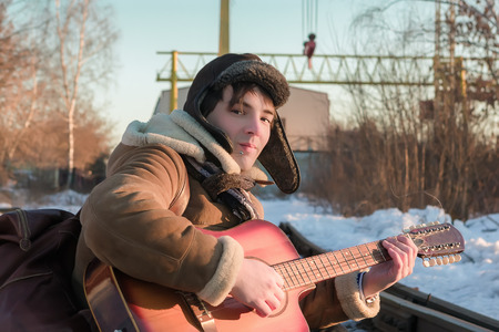 sheepskin: Young man in a sheepskin coat and hat with earflaps plays guitar sitting on railway tracks in winter.