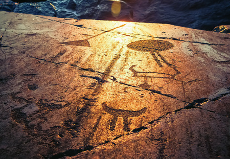 onega: Fragment of Onega petroglyphs on a granite plate at sunset. Age of object - 5000-6000 years. Russia, Karelia. Stock Photo