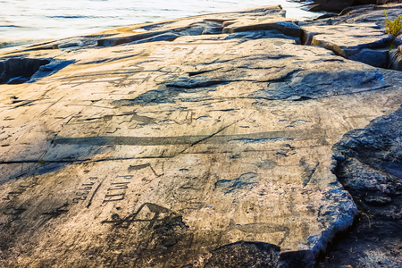 engravings: Attraction of Karelia is Onega petroglyphs on the sunset - prehistoric rock engravings (4th-2nd millennia BC) carved on the granite shore of the lake on the cape Besov Nos. Stock Photo