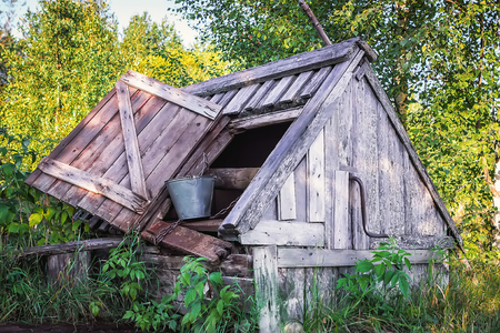 groundwater: Old wooden well with a roof and open door where stands the metal bucket with a chain on a background of foliage in the sunlight. Selective focus on the foreground. Stock Photo