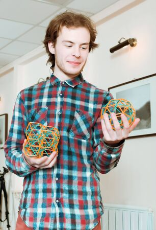 Young smiling man in a plaid shirt standing and holding coloured three-dimensional models of geometric solids. Stock Photo