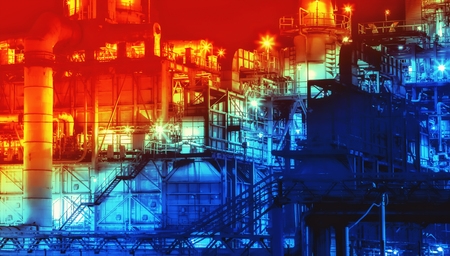Industrial background - scenic of oil refinery plant shines at night in orange and blue tones. Lens blur filter, toned.