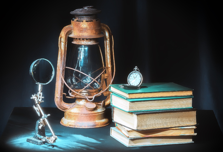 Still life in retro style on the dark background - books, kerosene lamp, clock and magnifying glass. Selective soft focus.
