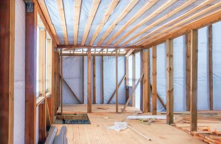 Frame construction of a wooden house using a vapor barrier. Inside view, selective focus. Archivio Fotografico