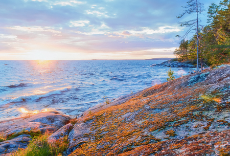 Rocky coast of Onega Lake at sunset in White Nights season - Republic of Karelia, Russia. Selective focus.