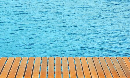 Orange wooden terrace planks of pier over blue ripple of the sea - background with space for copy.