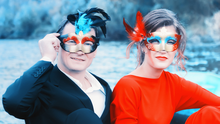 Colorful portrait of a young enamored couple in masquerade masks - man in a suit and woman in red against a blue lake. Focus on foreground. Stock Photo