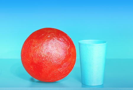 Red papier-mache ball and plastic cup on the turquoise and blue background - abstract geometric design with space for copy. Stock Photo