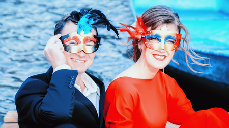 Red and blue portrait of a happy young couple in masquerade masks - elegantly dressed man and woman laughing against the lake. Focus on foreground. Stock Photo