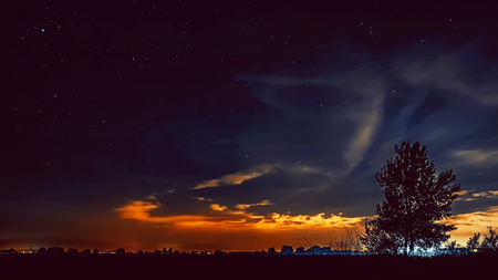 Beautiful night starry sky with Perseids over the countryside before dawn. Russia.