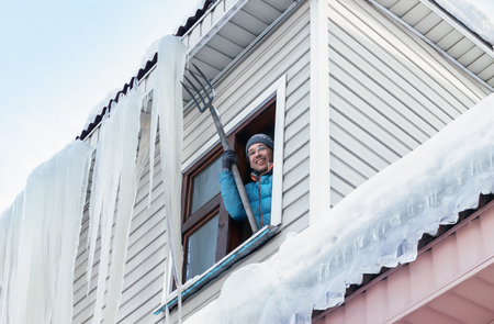 Smiling man removes giant icicles and snow from the roof using pitchfork through the window on a clear winter day. Bottom view, selective focus. Stock Photo