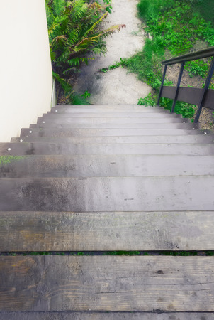 View from above to outdoor downstairs and path - old wooden staircase with handrail. Selective focus.