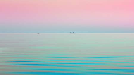 Atmospheric natural motion blurred background - turquoise waves of Onega Lake under the pink sky in the White Nights season. A small island and a boat are visible in the distance at the horizon. Space for copy.