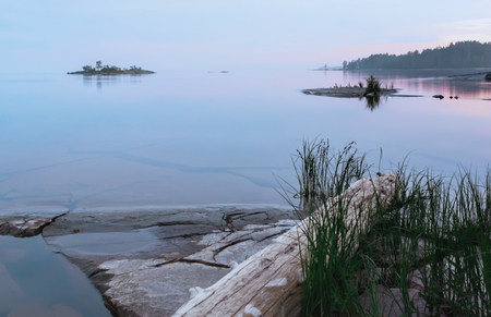 Small rocky islands with grass and driftwood among the clear waters of the lake at northern summer night. Reflection of the sky in mirror water. White Nights season in the Onega Lake - Karelia, Russia. Selective focus.