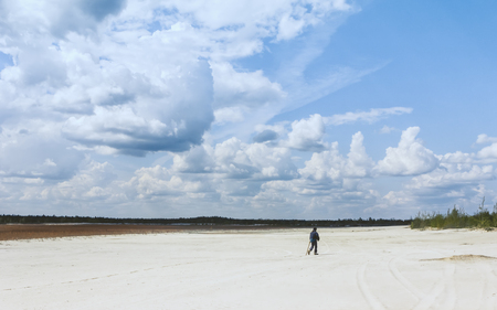 Aboriginal man in the distance walking across a sandy desert with sparse plants under a beautiful blue sky with huge cumulus clouds. Conceptual wide summer landscape. Selective focus.