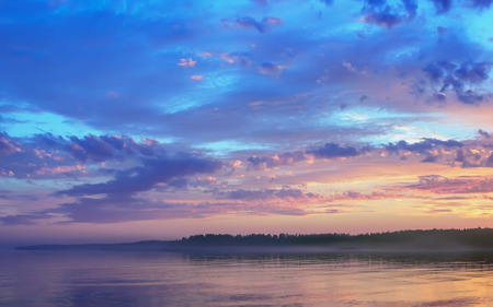Beautiful night sky with colorful clouds and floating mist over the golden water surface at sunset . Midnight on the forested shore of Lake Onega in the White Nights season. Republic of Karelia, Russia.