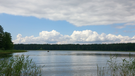 Cumulus and storm clouds in a dynamic sky over the forest lake at summer day. Concept of the fishing season. Lake Seliger, Russia. Selective focus, blurred vignette, space for copy.