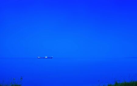 Cargo ship sailing on the horizon in the sea on a foggy blue night. Blurred dark marine background with space for copy, long exposure. Banco de Imagens
