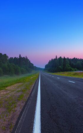 An empty straight asphalt road leads to a pink dawn under the cloudless blue sky in the misty summer morning. Russian federal highway A119. Selective soft focus, space for copy.