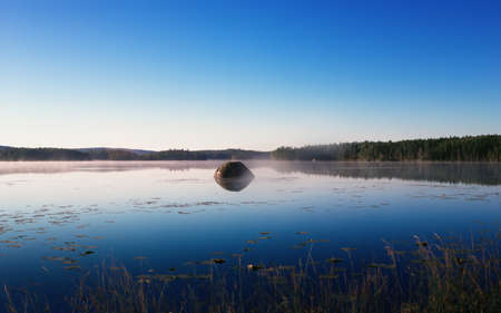Cool misty summer morning reflected in the northern forest lake. Large stone boulder island in the mirror water under a clear blue sky. Natural background with copy space, selective focus. Karelia.