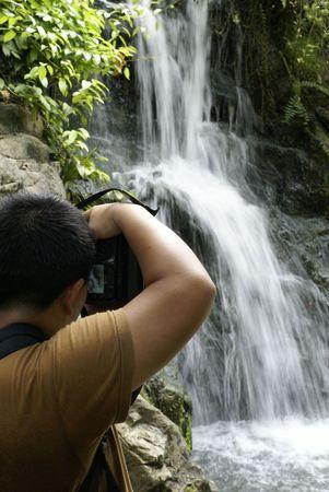 Tropical tourist taking photo of waterfalls photo
