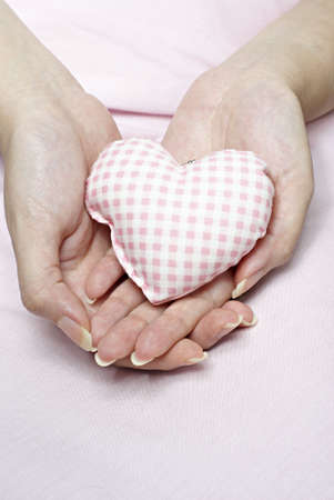 Love shaped cushion in hand Stock Photo - 4788919