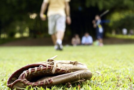 baseball catcher: People playing softball outdoors with focus on catchers glove on grass