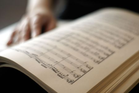 musical score: Female hand on musical score book page