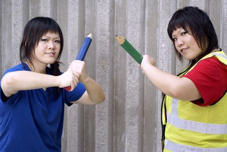 combative: Two asian teen girls with large pencils in combative stance, educational concept