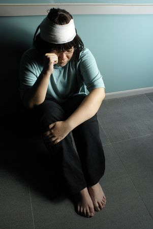 Injured and miserable teen girl unhappy crouched on floor Stock Photo - 5308679