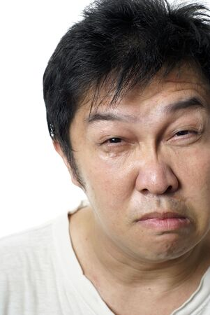 tormented: Miserable asian man portrait on white background Stock Photo
