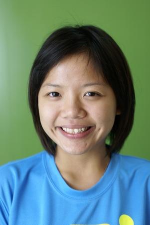Smiling female asian teen on green background photo