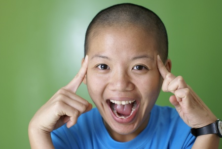 Happy asian girl point at bald head with fingers photo