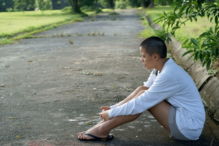 Sad bald asian woman seated on ground outdoors photo