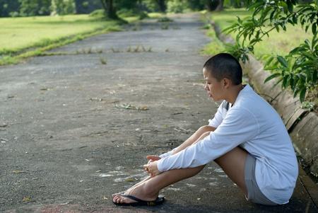 persona deprimida: Triste mujer asi�tica calva, sentada en el suelo al aire libre
