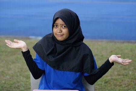 blase: Muslim asian girl with puzzled blase look