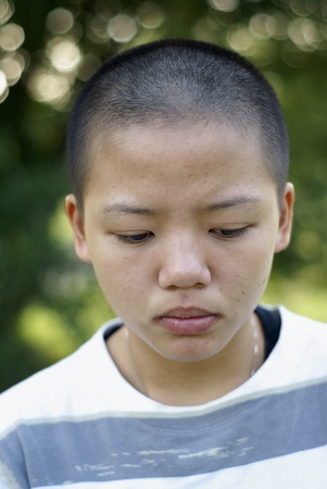 Sad asian teen girl with shaved head photo